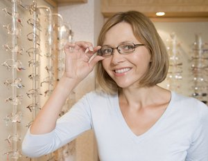 Woman trying on eye glasses frames